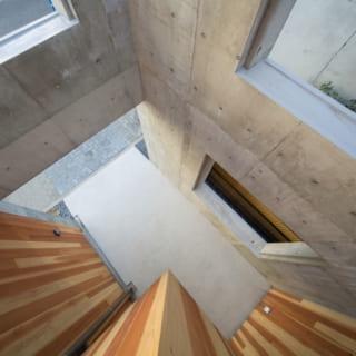 コンクリート外壁と木造建物の中間にあるスペースが、家の中から外を見たときの圧迫感を感じさせず、心に余裕を生んでくれる