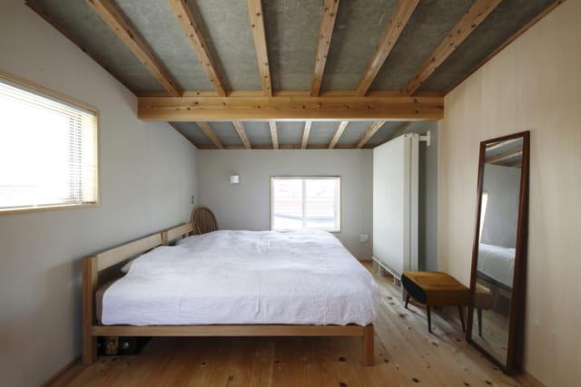 2階の主寝室。天井は低いところで1800㎜に抑えられ、屋根裏部屋のような雰囲気に。落ち着いてゆっくりと休める空間となっている