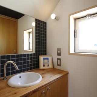 ダークな色のタイルと木の風合いが美しい1階の洗面所。窓も設けられており、十分な明るさがある。