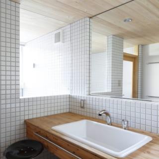こちらは白いタイルと木を合わせた洗面脱衣室。この奥にはバスルーム、そして背面にはトイレとランドリー室が一直線の短い動線で続き、行き来しやすさが配慮されている