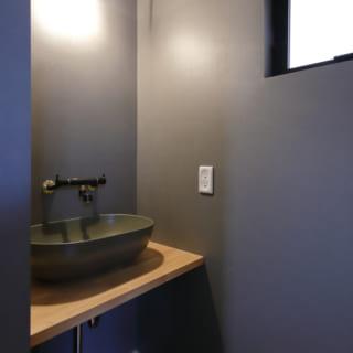 壁面、洗面台、蛇口を落ち着いた色合いで統一したシンプルで洒落た洗面所