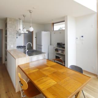 シンプルなしつらえのキッチンとダイニング。左手の黒い窓枠の向こうは玄関土間となっており、ダイニングの明るい光が土間も降り注ぐ