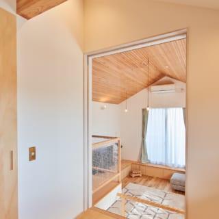 リビング側の2階洋室。開口の大きなガラス窓が、斜め下のリビングなど家中の空間とのつながりを生んでいる