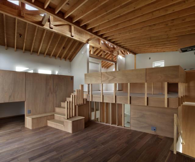 2階 リビング/階段の両脇にはシンプルなベンチがあり、棒の手すりはベンチの背もたれにもなるなど、楽しい遊び心が満載だ。階段右のフェンス状になった部分から下をのぞくと1.5階や1階が見えて冒険心をかき立てられ、お子様にとっては格好の遊び場に。写真右端にはリビングから1.5階へ下りる階段があり、家中をぐるりと回れるような造りになっている
