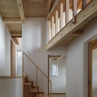 1階 階段まわり/1階は1mほど地面に埋められているが窓や上階から光が入り、閉塞感は皆無。写真奥は子ども部屋。写真右は主寝室の入口。写真左の階段を上がったところはバスルームや収納室がある1.5階。写真右上のフェンス状の部分は2階のリビングとつながっている