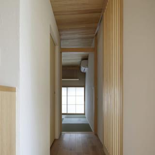 和室に向かう廊下。上をガラス戸にして天井が連結して感じられるよう上をあえて開けている
