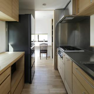 腰越さんが造作したキッチンにはナラ材を使用。正面にはリビング、後ろにはパントリーがある