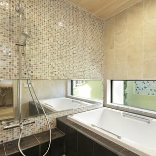 正面にモザイクタイルを用い、変化を付けたバスルーム。目線の高さに鏡を取り付けることで、空間を広く見せることができる