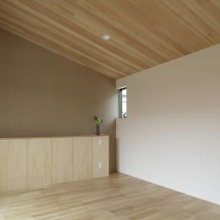 夫婦の寝室。正面はヘッドボード。床にはナラ材、天井にツガ材を使った落ち着いた空間