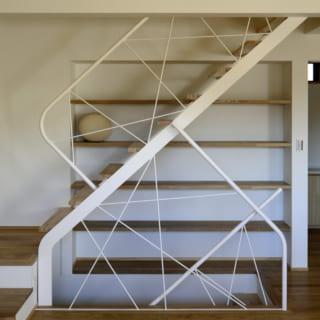 階段の手すりの不規則な模様は、四方に伸びる木の枝や蔓を連想させる。横のデットスペースも、棚として上手く活用