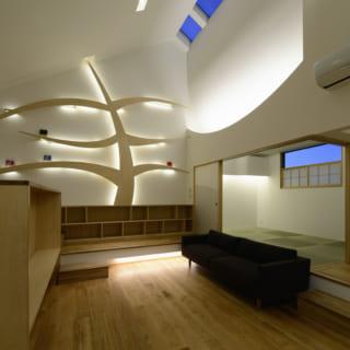 リビング奥の壁には、第二のシンボルツリー「知識の木」のオブジェ。本が果実のように実る本棚は、間接照明の役割も担っている