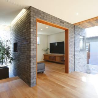 玄関側面の壁、リビング入り口の壁には外壁と同じタイルを貼ることで、そのまま外壁へと繋がって見える。外と内の境界を感じさせないデザインだ