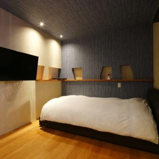 2階の主寝室は、思い切ったデザインのクロスを採用。造作カウンターに設けた、カタチが不揃いのニッチもアクセントになっている
