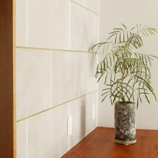 キッチンの背面のタイルはやや粗めのデザインのものにして、目地には真鍮を使用。目地の厚みを変えることで、陰影をつけている
