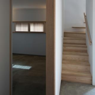 寝室の隣には2階に続く階段を配置。土間のモルタルと階段の木の風合いが違和感なく組み合わされている