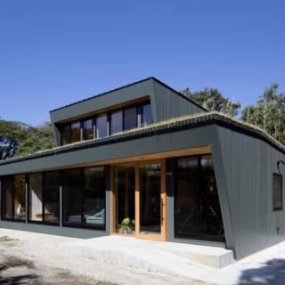 ガルバリウム鋼板が、周囲の緑と調和した外観。南面が全面ガラス張りになっており、明るく開放感のある建物となっている