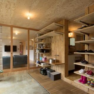 玄関は土間になっておりガレージのように使うことができる。右半分は棚を取り払い仕切りを設けることで部屋に作り変えることが可能な設計