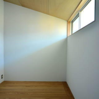 白い壁と木材のコントラストが美しい、シンプルなつくりの子ども部屋