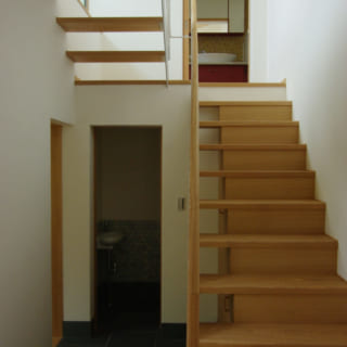 スケルトン階段にすることで、空間をより広く見せられる。階段下には造作棚を設けて、空間を有効活用