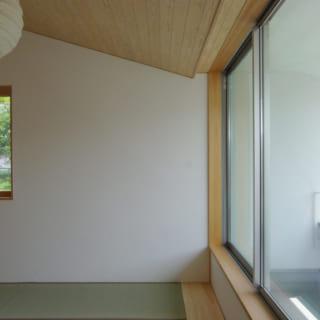 板張りの勾配天井、バルコニー側の大きなガラス窓など、爽やかな居心地を実現する2階和室