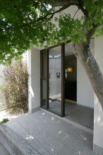 シックな木枠の玄関ドアはガラス張り。入ってすぐの応接ルームからは樹齢60~70年のモミジがよく見える