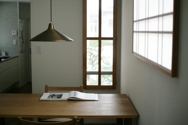 ダイニングテーブルはナラ材。照明は年々味わいを増す真鍮製。椅子に座ると視線が外に抜け、緑を眺められる