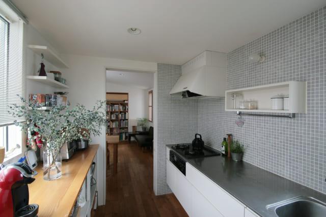 窓辺で料理を楽しめる2階のキッチン。木目と白、グレーのタイルでまとめた、清潔感と温かみのある空間