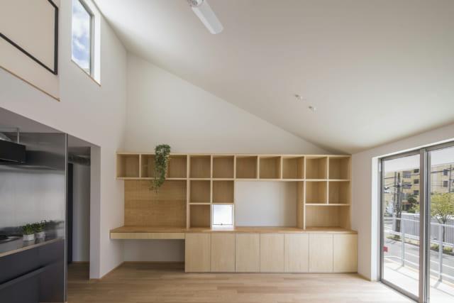 勾配天井で開放感あふれる2階のリビング・ダイニング。一面の壁にテレビ台や収納棚、お子さんが勉強できるカウンターなどが一体となった家具を造作。リビング・ダイニングには床暖房を入れているため、寒い冬でも快適に過ごせるとか