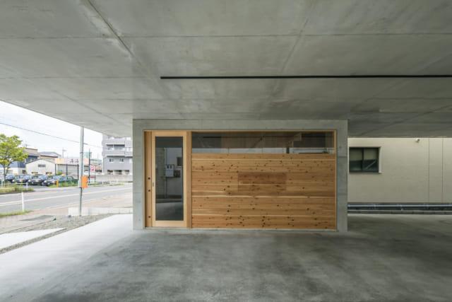 木枠、杉板貼りで、引き戸になっている玄関は、防犯性の高い電子錠を採用。杉板貼りの壁の中央は開閉式になっており、開けると網戸に。中間期は、ここを開けることで建物全体の風通しをよくしてくれる