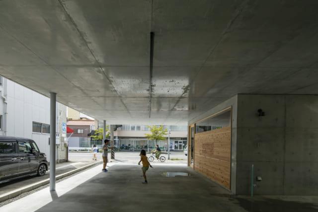 屋根のある駐車場スペースは車2台が余裕で停められ、玄関から奥の仕事部屋までピロティが繋がる広さ。雨の日は、お子さんの遊び場にもなる