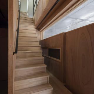 上部に明り取りのガラス窓があり、壁の中央部には網戸付きの開閉式窓もある玄関ホール。階段の奥は土間収納に