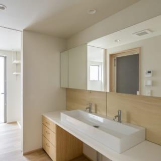 造作の洗面化粧台は、家族4人が並んで歯磨きしても余裕の広さ。3枚が並ぶ大きなミラーのうち、左右のミラーの裏側が収納になっている