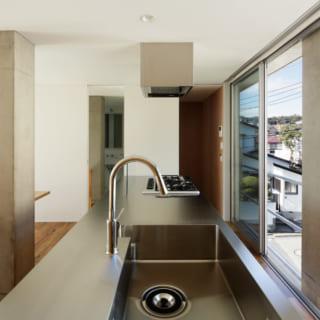 シンクの丸みを極力抑えたキッチンは、特注の品。中央にそびえる柱と一体化したベンチの直線が美しい
