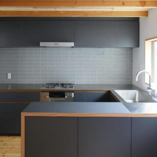 ダイニングに設置されたキッチン。コの字型のカウンターには、ステンレスとメラミン化粧板を貼り分けてデザイン。