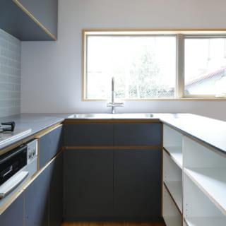 建物全体にも使用しているキーカラーのブルーグレーを使用。食器棚はオープンにしてコストダウンをはかった