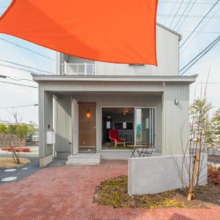 A棟の外観。玄関を入ると土間リビングが広がる。軒が1.8mと深いので夏の強い日差しを遮る効果も。遊歩道からの出入りも可能だ