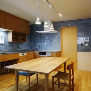キッチン、ダイニングテーブルは家具屋さんの手によるオーダーメイド。素材にタイルを多用したデンマーク風のキッチンは、茶色系のさし色もあしらって北欧風の色合いに