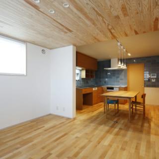 床と天井のウッドに挟まれ、白い漆喰壁の風合いも引き立つナチュラルテイストのLDK。リビングの天井高は2300mmとやや低め。キッチンスペースの天井高は2500mmと、あえて高さに違いを生むことで、空間の切り替えを表現した