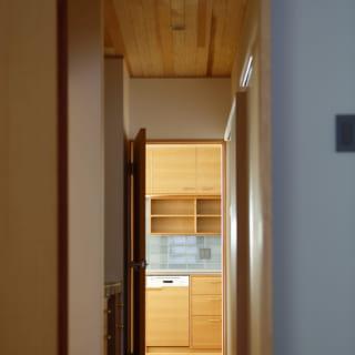 主寝室からキッチンを見たときに、キッチンのタイルと色の統一感が生まれるよう、主寝室の壁のクロスはブルーグレーに
