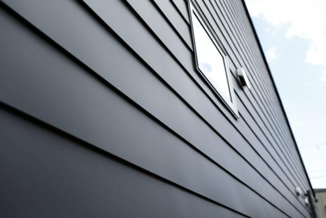 外壁は屋根材と同じガルバリウム鋼板を採用。横に長いガルバリウム鋼板の一枚板を上下に並べて張っていくことで横のラインが際立ち、横に大きく広がる背景の多度山の雄姿とのバランスもいい