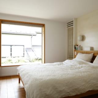 2階主寝室。木製の窓枠が、シンプルな白い部屋によく映える。窓を開け放しておくこともできるよう、左側に細い通気用の窓も設けている。窓の外は洗濯物などを干せるバルコニー