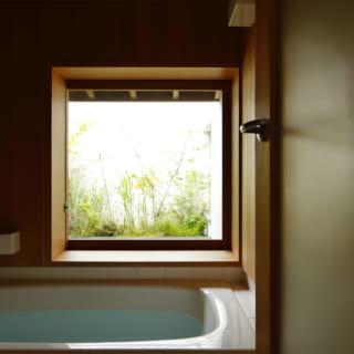 2階バスルームも、木の温かみが漂う心地よい空間。窓越しの緑を眺め、ゆったりと入浴できる