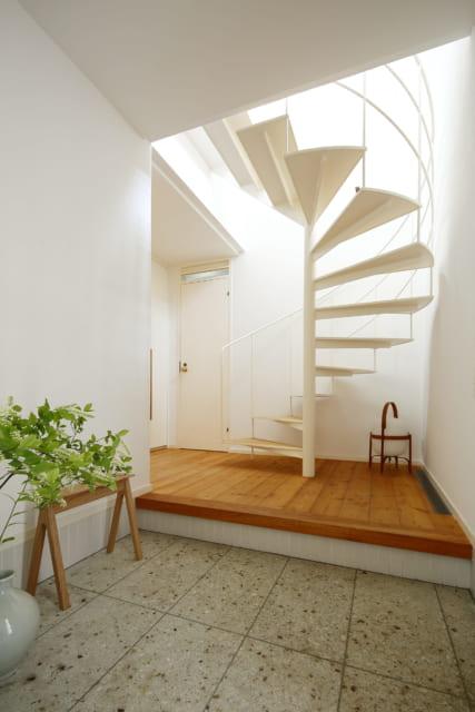 1階玄関で西を見る。明るい光が落ちてくる吹抜けのらせん階段が、洗練された空間をさりげなく演出する