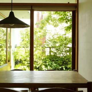 1階リビング&ダイニングのテーブルは南の庭に面しており、外とのつながりを感じられる居場所。窓枠は屋外の緑と馴染む木製で統一