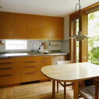 1階キッチン。南の庭に面した大きな窓の横にダイニングテーブルを配してあり、テラス感覚で食事ができる。窓の一部はガラス扉なので自由に庭へ出入りでき、夏場に外でバーベキューを楽しむときの動線も抜群。造作したキッチンカウンターや収納は、熊澤さんのオリジナル
