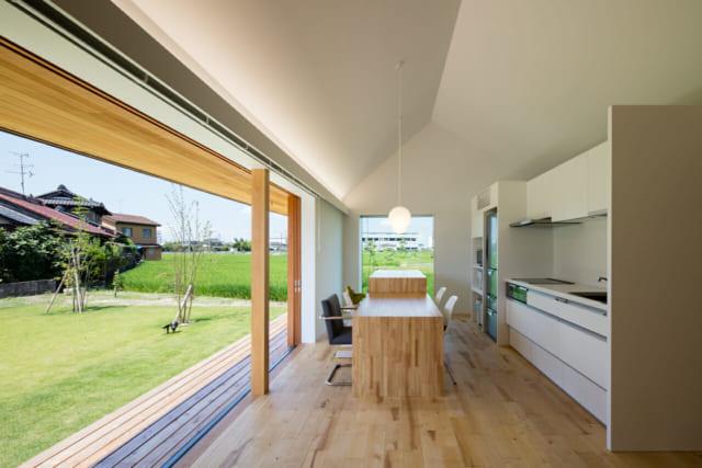開放的で風通しが申し分なく、気持ちよく過ごせるダイニングキッチン。画像奥、西側の窓はLow-E複層ガラスを使用することで西日の問題を解決し、眺望を楽しめるように。テーブルは造作で、奥の一段高い部分は作業台になっており、日常的に使う鍋や皿、調理家電などを収納する