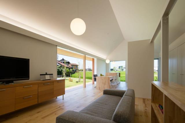 奥のダイニングキッチン、手前のリビング、右側にあるコモンシェルフは、家具や柱で緩やかに仕切られているが、天井は繋がっているため空間に一体感がある。照明の光は天井の勾配に反射し、優しく広がる。調光可能な間接照明と組み合わせれば、さまざまな雰囲気をつくり出せる