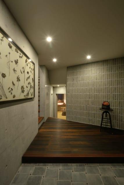 玄関は打ちっぱなしのコンクリートとタイル張りのクールな壁の表情が印象的。玄関内の籠目張りタイルにもこだわりが