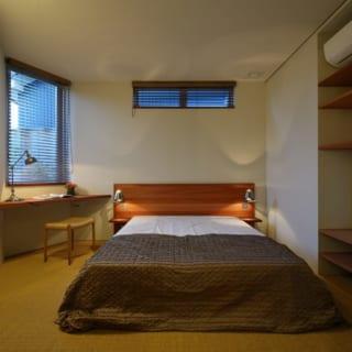 寝室。床はサイザル麻のカーペット。作り付けの棚の裏がウォークインクローゼットになっている