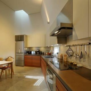 長さが際立つキッチン。収納スペースをしっかり設けて、吊り棚も壁一面に設置することで、食料庫や食器庫をも兼ねている